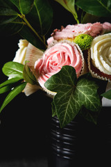 Bouquet of cupcake and green leaves in a black flowerpot. Dark background. A gift to the girl.