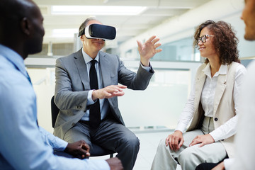 Mature business leader in vr goggles telling his subordinates what he sees in another reality