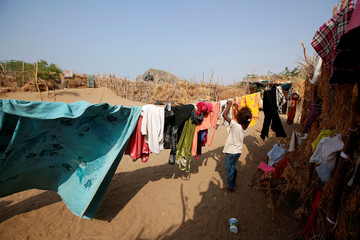 A girl hangs up laundry near her family hut at a poor neighbourhood on the outskirts of the Red Sea port city of Hodeida