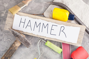 Inscription HAMMER on torn paper on wooden plank beside building tools on background of gray dirty cement