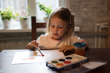 A little girl  drawing with watercolors