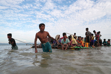 Rohingya refugee men pull the raft as they cross the Naf River with an improvised raft to reach to Bangladesh in Teknaf