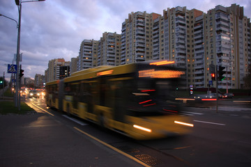The motion of a blurred bus on the street at dusk