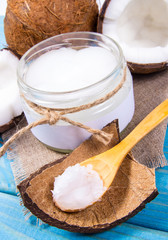 Coconut oil and fresh coconuts on a wooden table.