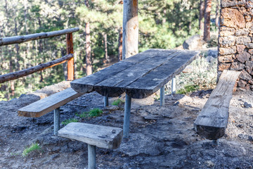 Table and wooden benches in an outdoor hut, where to rest and eat