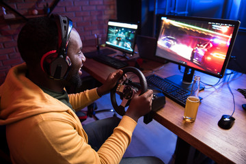 Top view of optimistic african man in headphones is playing car racing video game with steering wheel on modern computer. He is sitting at table and looking at screen of monitor with smile