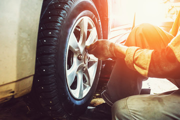 Car mechanic worker doing tire or wheel replacement in garage of repair service station