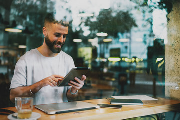 Half length portrait of handsome young successful businessman enjoying tasty tea in a modern coffee shop and holding digital tablet in his  hands to read business news review in the internet.