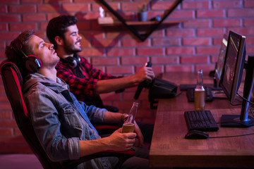 Profile of young gamers are sitting at desk. Focus on sleeping guy is resting in chair with bottle of beer. Cheerful bearded man is enjoying car simulator with steering wheel in background. Copy space
