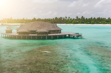 Luxury thatched roof honeymoon bungalow in a vacation resort in the blue lagoon of the Indian Ocean in Maldives. Piece of paradise. Good choice for vacation. Beautiful top view for wallpaper.