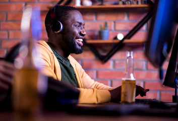 Lets win. Profile of joyful african gamer in headphones is playing on computer while sitting at table with beer and expressing gladness. He is spending time at home with pleasure