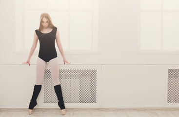 Beautiful ballerina stands near window