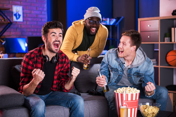 Goal. Delightful friends are watching tv and shouting joyfully while celebrating win of their football team. They are sitting on sofa, eating popcorn and drinking cold beer while expressing happiness