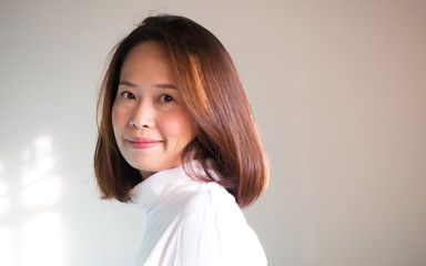 Chubby asian woman in white Turtle Neck T-shirt smiling. Portrait on white background with nature light. Copy space.