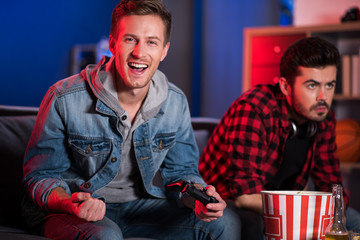 I am champion. Portrait of happy young guy is holding joystick and celebrating his win. He is sitting on sofa and expressing gladness while looking at camera with smile. His friend in background