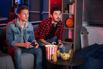 Weekend entertainment. Involved trendy cute guys are sitting on couch and holding joystick while playing home video games. They are looking at screen absorbedly. Copy space in the right side