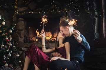 Joyful couple near christmas tree and fireplace with bengal lights selebrate New Year