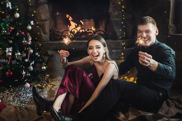 Joyful couple near christmas tree and fireplace with bengal lights selebrate New Year