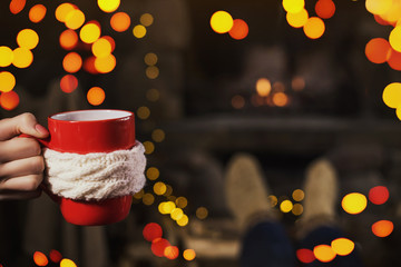 female hand  keeps red cup of tea on the fireplace background
