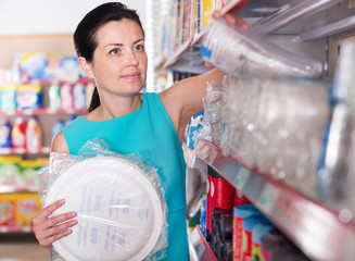 Female buying to disposable tableware at supermarket