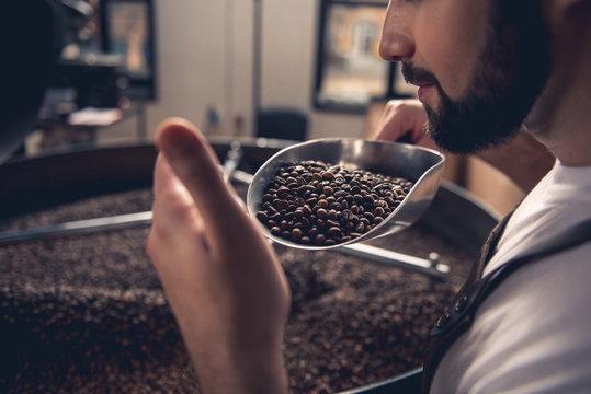 Serene bearded man enjoying burned beans aroma while holding them on spatula. Industry concept. Close up