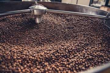 Aromatic coffee beans situating in modern roaster machine with grain chiller. Industry concept. Close up