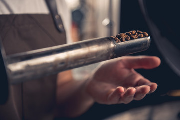 Close up arm of master checking different degrees of roasting coffee with special scapula stick. Monitoring concept