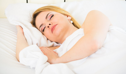 Blonde girl sleeping on white pillow in bed at home