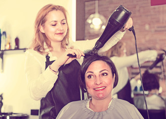 Hairdress master is combing and drying hair to smiling woman