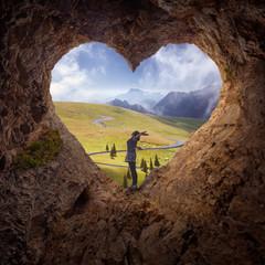 Lone woman in heart shape cave towards the idyllic scenery