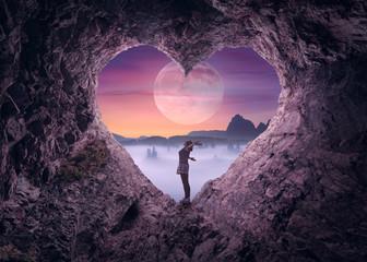 Single woman in heart shape cave towards the idyllic scenery