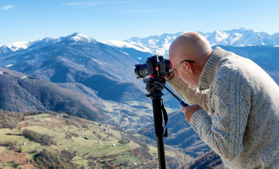 photographer with digital camera on top of the mountain