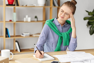 Fatigue overworked female enterpreneur writes noted in notebook, keeps hand on head, has headache after long work at office, has much things to do, sits over shelf with books. Overworking concept