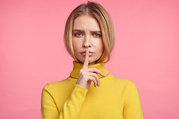 Attractive woman keeps fore finger on mouth, shows silence sign, asks people to be quiet, not interrupt. Young female model says not to tell secret, gestures indoors, has serious expression.