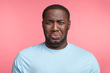 Black man has sorrorful miserable expression being depressed after fired on work, cries, has stressful situation, dressed casually, isolated over pink background. Plump unshaven African man in panic
