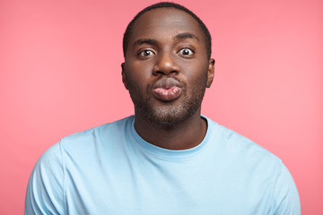 Pleasant looking African American man rounds lips, going to recieve kiss from beautiful girl, being in anticipation of pleasant moment. Attractive black man sends kiss for you. Sympathy and feelings