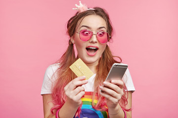 People and technology concept. Adorable cute chick girl holds credit card and modern mobile phone, transferr money on account, looks surprisedly into screen. Mobile payments. Online shopping.