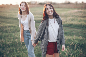 Two young women walking and holding hands at the sunset. Best friends.
