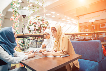 islamic girl sitting at table in cafe