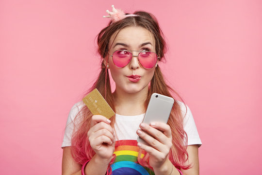Horizontal portrait of female chick has dreamful expression, imagines new clothes, going do online shopping, holds modern cell phone and plastic card, isolated over pink background with copy space