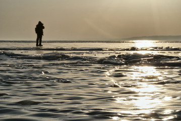 a photographer on the ice of lake Baikal makes a photo of the sunset