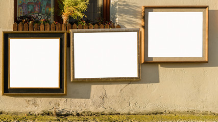 Three picture wooden frames on the facade of old building during sunset, Blank White Isolated Clipping Path