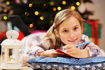 Happy Girl Writing Christmas Letter to Santa Claus