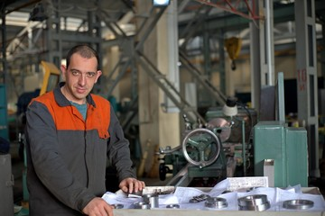 metalworking industry: factory man worker in uniform working on lathe machine in workshop