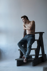 Cute young shirtless 20 something male model in denim on a wooden ladder on a white background