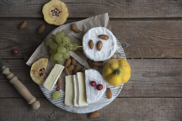 camembert cheese, fruits and nuts on the wooden table