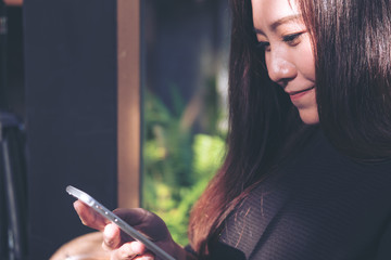 Closeup image of a beautiful Asian woman with smiley face using and looking at smart phone in modern cafe