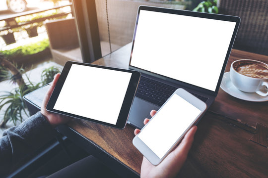 Mockup image of a businesswoman holding white mobile phone , black tablet and laptop with blank white screen on vintage wooden table with coffee cup in cafe