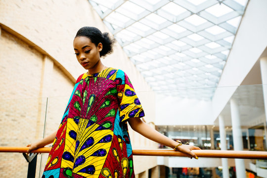 Fashion african woman in national dress holding on handrail at shopping center. People and lifestyle concept.