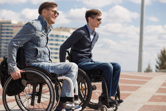 young man sitting on a wheelchair with his friend